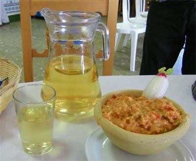 Jarra de mosto con su vaso en el Mosto Domi de Jerez. A su lado un plato de ajo caliente, la comida típica para acompañarlo.