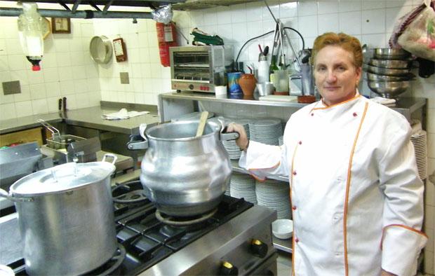 Dolores Díaz posa en su cocina con la olla en la que hace su magnífica berza. La sirven también como tapa en la barra. Foto: Cosas de Comé.