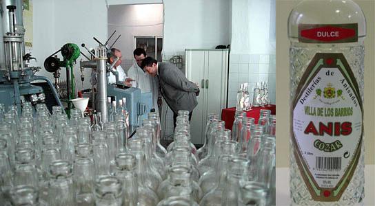 Un aspecto de la fábrica y una botella de Anís Cózar dulce.