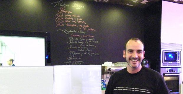 Javier Vélez delante de la peculiar carta de la tienda escrita en tiza sobre la pared negra. Foto: Cosas de Comé.