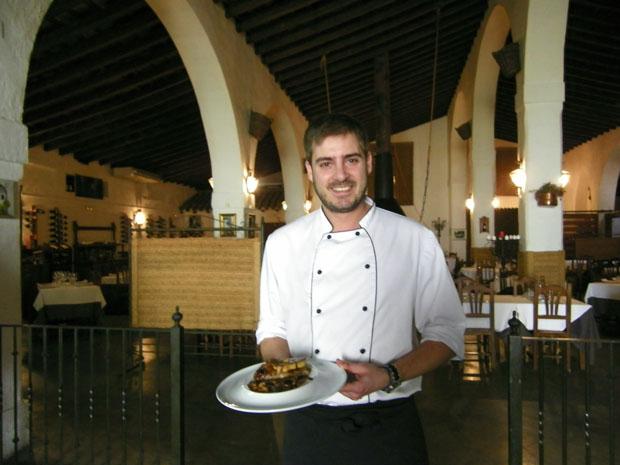 Javier Muñoz, jefe de cocina de La Carboná, con su plato de manitas en el comedor de La Carboná. Foto: Cosas de Comé.