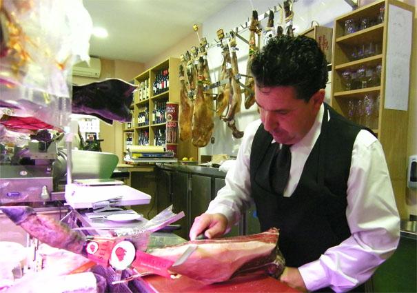 """José María García Gómez corta un jamón """"a cuchillo"""" en su tienda de Jerez, Caprichos del Gourmet. Foto: Cosas de Comé"""