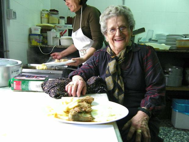 Teresa Montero en la cocina de El Soldao. Detrás, su ayudante Ana Rojas prepara unos huevos fritos con papas. Foto: Cosas de Comé.
