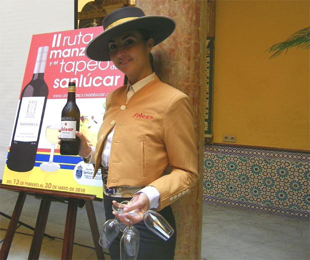 Una azafata se dispone a servir unas copas de manzanilla ante el cartel de La Ruta. Foto: Cosas de Comé