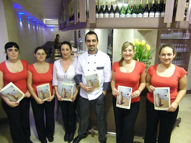 El equipo de Garum, con Carmen y Santiago Braza, en el centro de la foto, posa con la carta de tapas del bar. Foto: Cosas de Comé