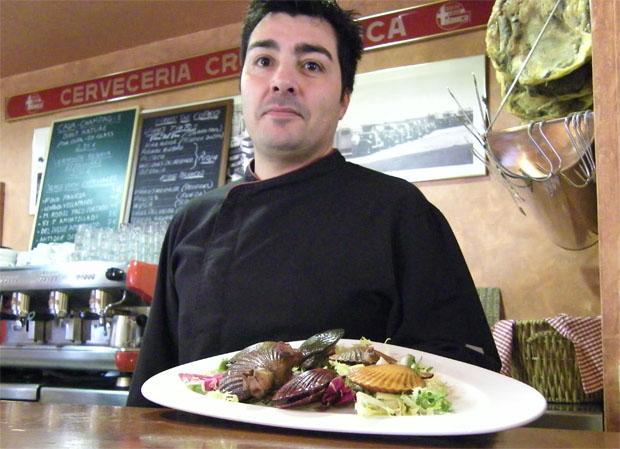 Julián Olivares, el cocinero de la Cruz Blanca, en la barra del local con una fuente de zamburiñas. Foto: Cosas de Comé