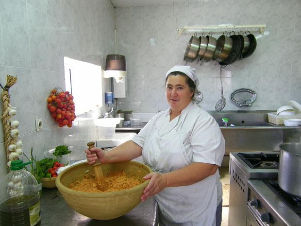 Ana María Puerta con el impresionante dornillo en el que prepara el ajo caliente. En la pared pueden verse colgados los tomates de viña, un cultivo casi extinguido en Jerez. Foto: Cosas de Comé