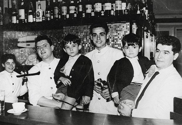 Emilio Sancho Mejías, el primero por la derecha con su hijo Luis en brazos, tras la barra del Bar Piccola. Emilio fue el inventor de la famosa ensaladilla del Piccola. Foto cedida por el bar Piccola.