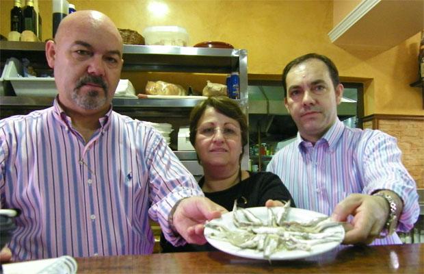 Los hermanos Gago con la cocinera de El Pescaíto, Concepción Garrido, posan con una fuente de boquerones listos para freir. Foto: Cosas de Comé.
