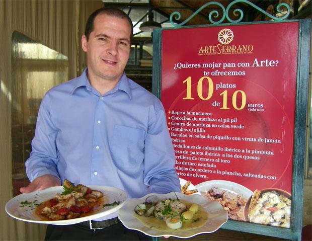 El encargado de Arteserrano Fran Renda porta dos de los platos de las jornadas junto al cartel que anuncia la promoción. Foto: Cosas de Comé