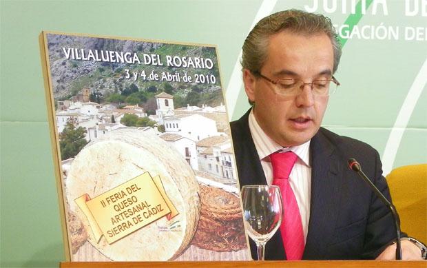 El alcalde de Villaluenga, Alfonso Moscoso, junto al cartel anunciador de la II Feria del Queso de la Sierra de Cádiz. Foto: Cosas de Comé