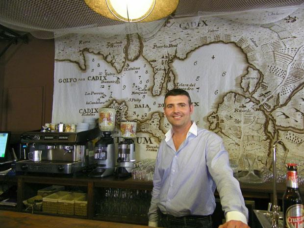 Juan Antonio López tras la barra de Marinero en Tierra y con el mapa de la Bahía de Cádiz antiguo tras él. Foto: Cosas de Comé