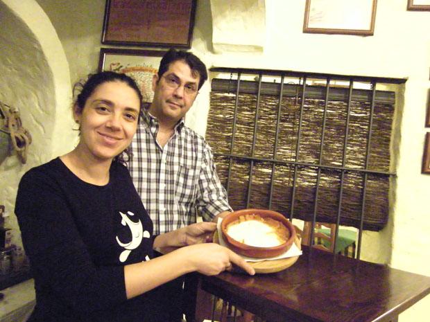 María de las Aguas Orellana, junto a su marido Antonio de Padua González Benitez, que se encarga de antender el mesón, en el comedor de su establecimiento con un plato de abajao. Foto: Cosas de Comé