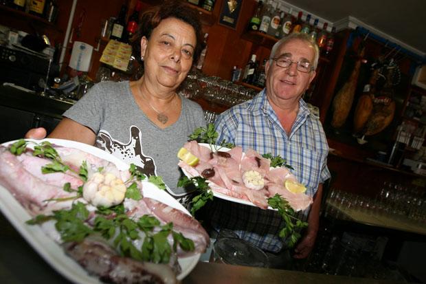 Regla Manzano y Manolo Márquez, los fundadores del Bar La Dorada de El Puerto con dos de sus productos más famosos, los chocos y los fileltes de marrajo, que hacen a la plancha. Foto: Victor López.