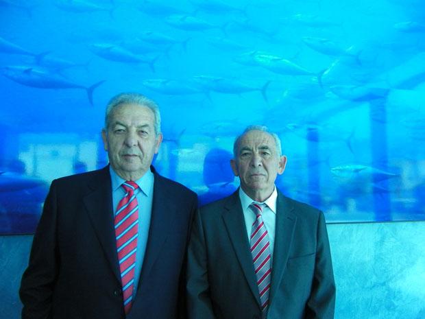 Los hermanos Pacheco, fundadores de Herpac, delante de una gran foto de atunes que preside la tienda colocada junto a la nueva fábrica. Foto: Cosas de Comé