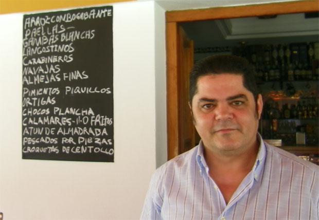 Juan José Torrejón, propietario de la Marisquería Porfirio, posa junto a la carta del establecimiento escrita a tiza y con todo un recital de clásicos de la cocina de la costa. Foto: Cosas de Comé.