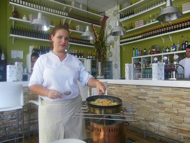 Una de las camareras de Show de tapas prepara un flambeado delante de unos clientes. Foto: Cosas de Comé