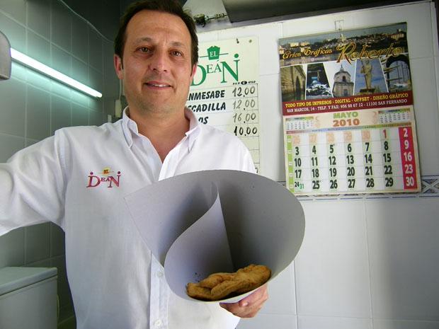 """Pepe Oneto con uno de los tradicionales cartuchos o """"papelones"""" de pescado de papel de estraza con el que se sirve el pescado en los freidores"""