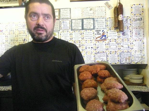 """José Cubiles en el bar La Tasca con sus bolas de """"masita"""" listas para poner en la plancha. El bar está decorado con azulejos con refranes y frases simpáticas. Foto: Cosas de Comé"""