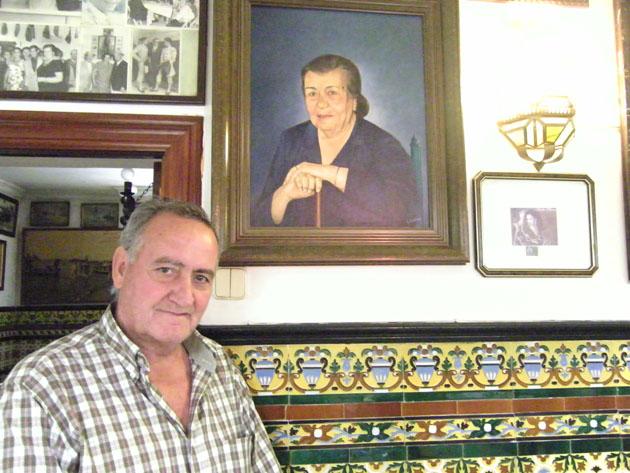 En esta foto Manolo Picardo, uno de los nietos de Catalina Pérez, y uno de los que actualmente hacen las papas aliñás. En la foto aparece junto a una pintura de su madre María Picardo, la hija de Catalina Pérez y la cocinera más conocida del establecimiento. Foto: Cosas de Comé.