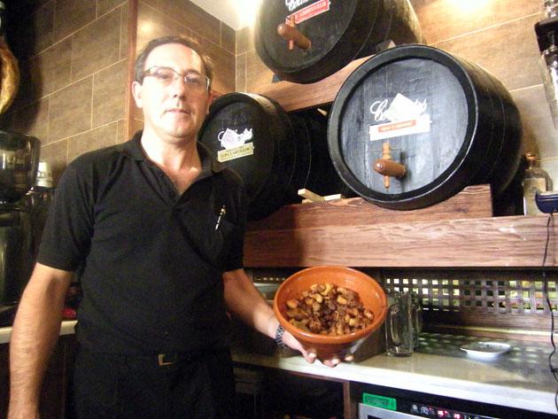 Rafael Montero con un lebrillo de chicharrones delante de las botas de vinos de Chclana de la bodega Collantes. Foto: Cosas de Comé