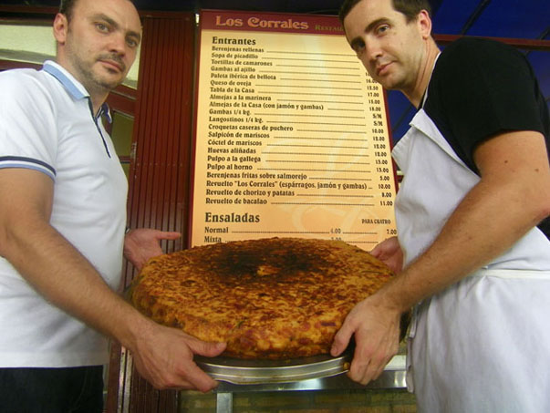 Paco San Nicolás, uno de los propietarios de Los Corrales y el cocinero Rafael Campos sostienen la impresionante tortilla mixta de Los Corrales que inventó y sigue realizando Manuel Rangel Macias, el fundador del establecimiento. Foto: Cosas de Comé.