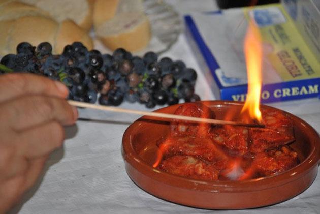 La longaniza, cortada en loncha gruesas se hace con alcohol al que se le prende fuego. Luego se come con pan. Es uno de los singulares platos tradicionales que probaremos durante la cata. Foto: Sebastián Gómez