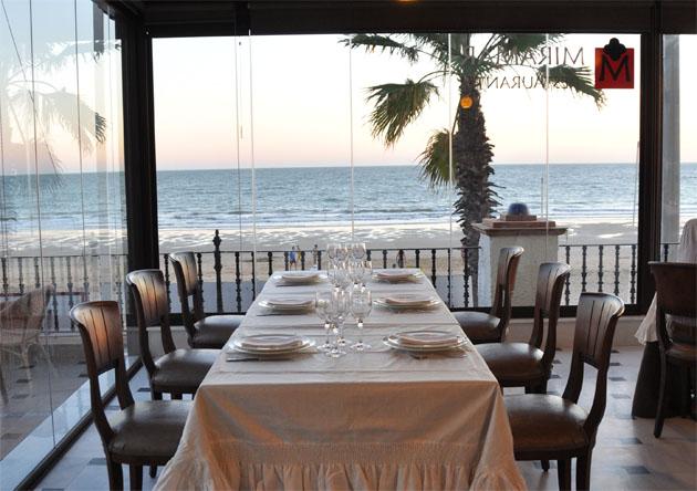 El comedor del restaurante Miramar, con la playa de Regla de Chipiona al fondo. Foto: Cedida por el restaurante Miramar