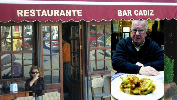 Manolo Valiente con un plato de perdices, uno de los guisos famosos del Bar Cádiz, cuya fachada aparece detrás. Foto: Cosas de Comé.
