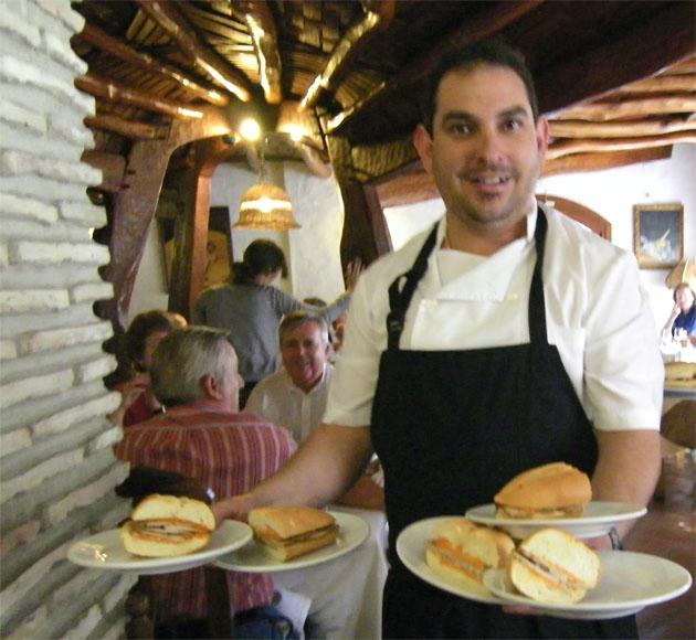 Un camarero de la Venta Pinto de Vejer con varios bocadillos de su famoso lomo en manteca. Foto: Cosas de Comé.