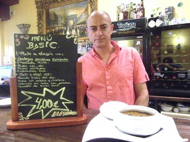 José Ramón Pages, gerente de El Escenario, junto a uno de los platos del menú, unas lentejas, y una pizarra anunciando el nuevo menú. Foto: Cosas de Comé