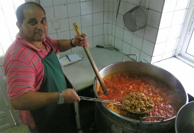 Manolo Melero dando los últimos toques a un guiso de almuerzo campero. En una mano porta una pala de madera con la que constantemente mueve la carne para evitar que el guiso se pegue. Foto: Cosas de Comé.