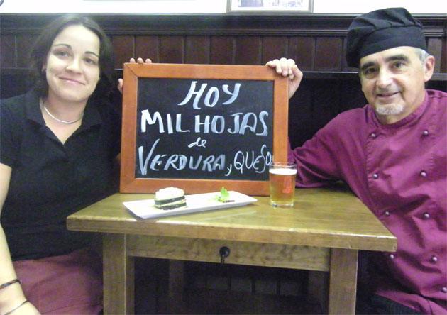 Ana Zamora, propietaria de El Cañón y Luis Ripoll, cocinero, con una pizarra en la que anuncian uno de los estrenos de la nueva carta. Foto: Cosas de Comé.