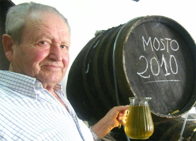 José Silva junto a uno de los barriles con el mosto de 2010 y una jarra de litro en la que se sirve. Foto: Cosas de Comé.