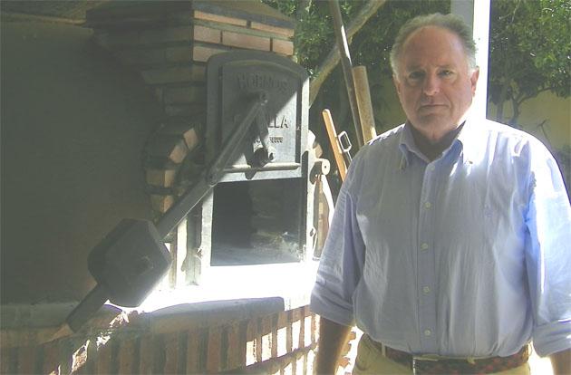 Juan José Borrero, propietario de El Molino del Conde, junto al horno de leña donde se realizan los asados del restaurante. Foto: Cosas de Comé.