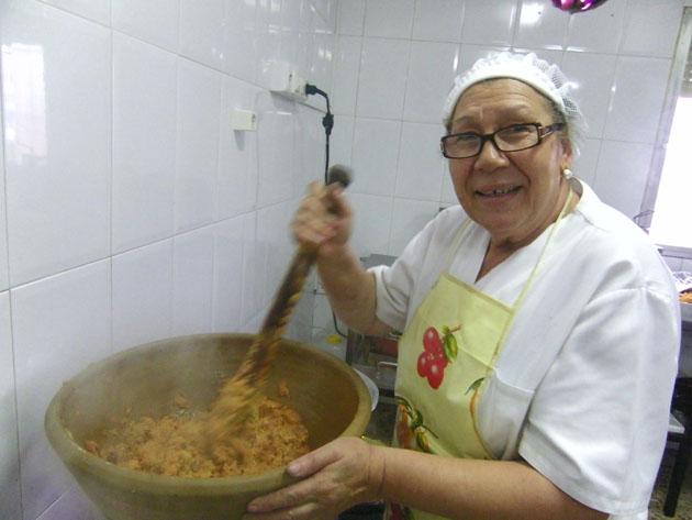 Ramona Valencia, la cocinera del Mosto Tejero, elaborando el ajo caliente en el típico dornillo y con su machacaera para ir majando la sopa. Foto: Cosas de Comé.