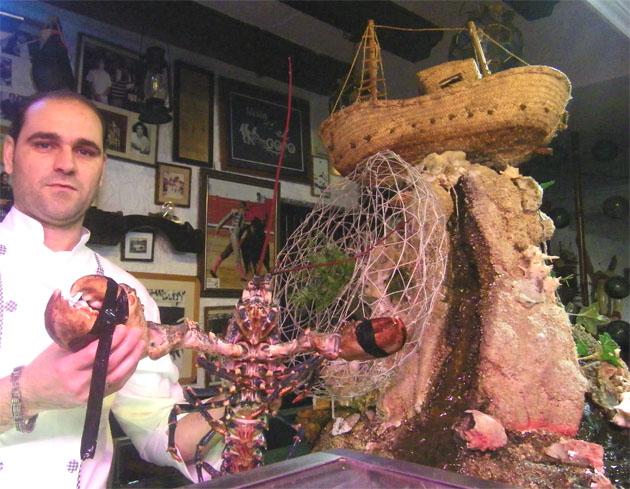 El segundo jefe de cocina de El Copo, Camilo Correro, con un bogavante vivo acabado de salir de una de las peceras del restaurante. El marisco se prepara al gusto del cliente. Foto: Cosas de Comé.