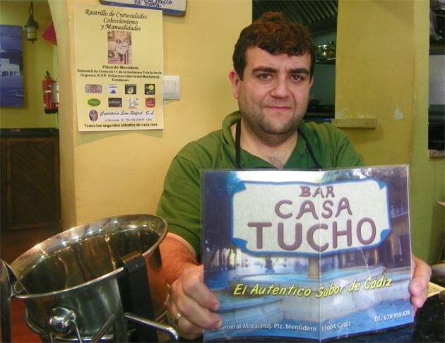 Esteban Sanles con un carte de su bar en el que anuncia cocina con el auténtico sabor de Cádiz. Foto: Cosas de Comé