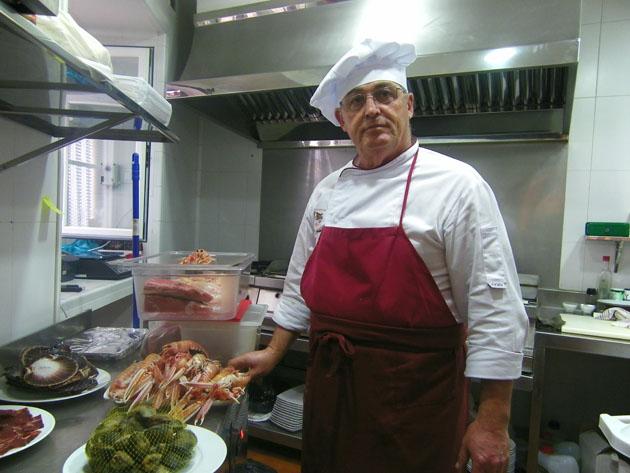 El cocinero José Ramón Jímenez en la cocina de La Posada con el género preparado para la plancha. Foto: Cosas de Comé.