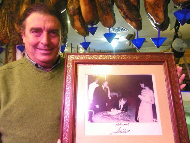 Manolo Moreno con la foto, dedicada por Don Juan Carlos, que recoge la primera vez en que atendió a Sus Majestades en el Campo de Gibraltar. En la instantánea Manolo aparece, a la izquierda de la foto, de pie y con chaquetilla blanca. Foto Cosas de Comé