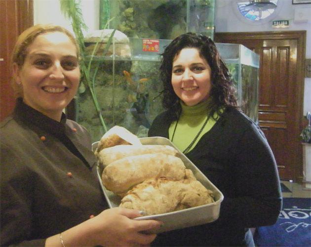 Vanessa Moreno, junto a su hermana Gemma Moreno, que se encarga de atender las mesas, con una bandeja de pan que hace ella misma para el restaurante. Foto: Cosas de Comé.
