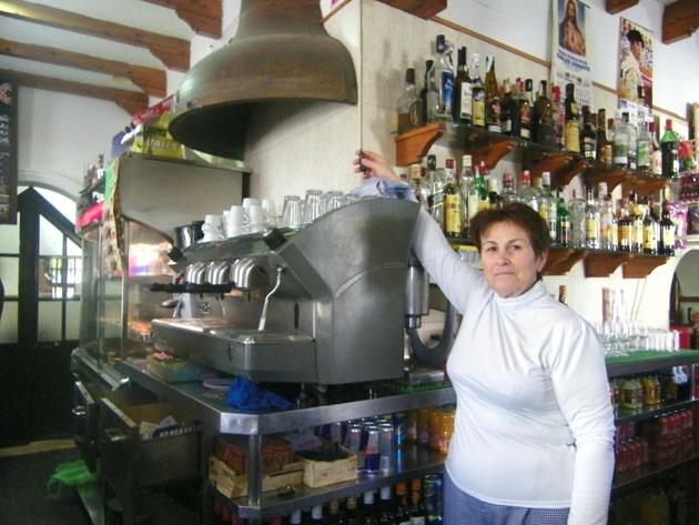 Amalia Rodríguez, la cocinera del Bar La Campana, junto ala gran campana que preside la barra del local. Foto: Cosas de Comé.
