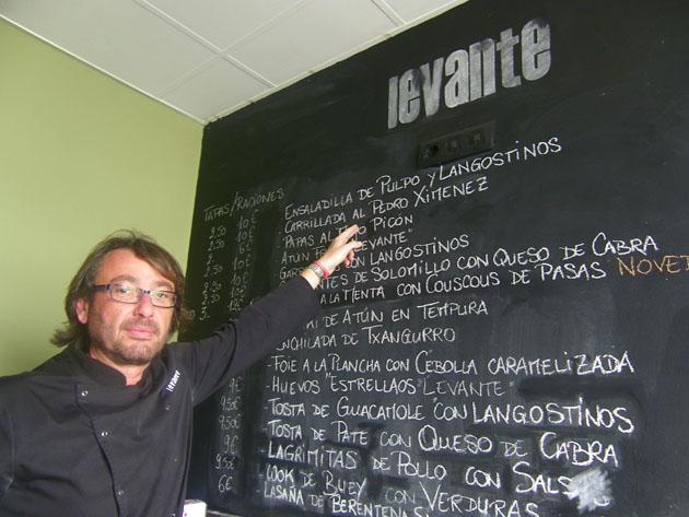 El cocinero Carlos Municio señala la ensaladilla en su carta de tapas y platos que tiene escrita en una inmesa pizarra en el bar. Foto: Cosas de Comé.