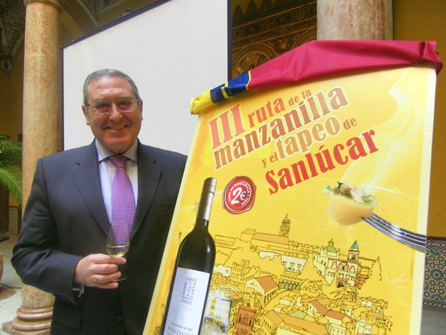 Jorge Pascual con cartel III Ruta de la Manzanilla y el tapeo
