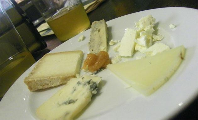 Plato de degustación de quesos en la Sidrería de El Pópulo. Detrás un vaso de sidra. Foto: Cosas de Comé.