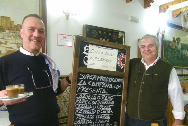 Tomás Luna, el camarero del Bar La Campana que hace los simpáticos carteles que anuncia las tapas del establecimiento junto a Pedro Arocha, el propietario del bar. Foto: Cosas de Comé.