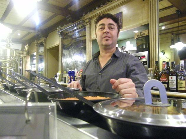 """Antonio de La Luz Bolaños """"Tino"""" tras las sartenes que tiene en la barra para mostrar sus guisos. Foto: Cosas de Comé"""