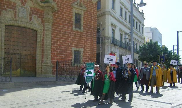 Representantes de las cofradías gastronómicas andaluzas desfilan por delante de la Iglesia Mayor en la calle Real de San Fernando. Foto: Cosas de Comé