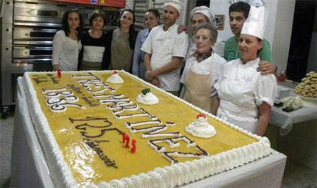 Los Martinez con la inmensa tarta que hicieron para conmemorar el 125 aniversario de la pastelería. Foto: Cedida por pastelería Martínez.