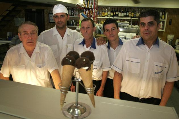 Gianni Campo, el primero por la izquierda, junto a su personal de la heladería Los Italianos. Delante los populares topolinos de chocolate. Foto: Cedida por La Voz de Cádiz.
